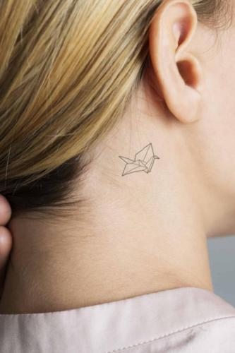 Closeup of a simple behind the ear tattoo of a young woman